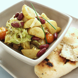 Indisk curry med kål og kartofler serveret med naan