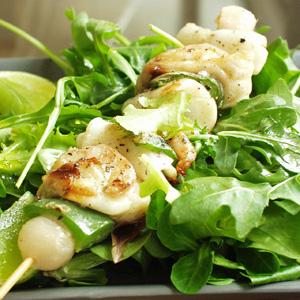 Spid med blæksprutte og rejer serveret med salat